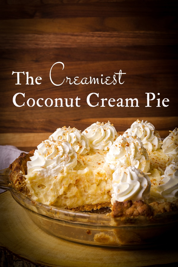 A coconut cream pie with a slice taken out of it.