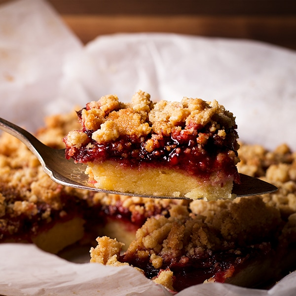 Lifting a cherry shortbread crumble bar from the pan with a spatula.
