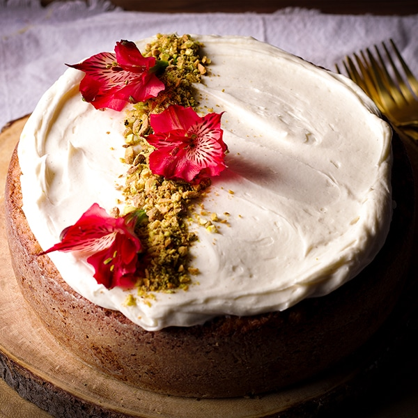 A Pistachio Cardamom Cake frosted with Cream Cheese Buttercream on a wooden tray.