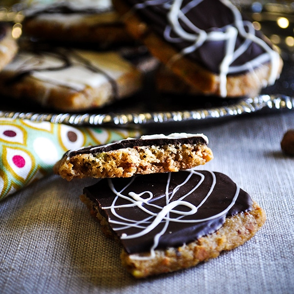 A double chocolate pistachio shortbread cookie, broken in half so you can see the buttery, nutty, crispy center.