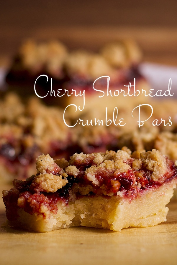 A cherry shortbread crumble bar on a tray with a bite taken out of it.