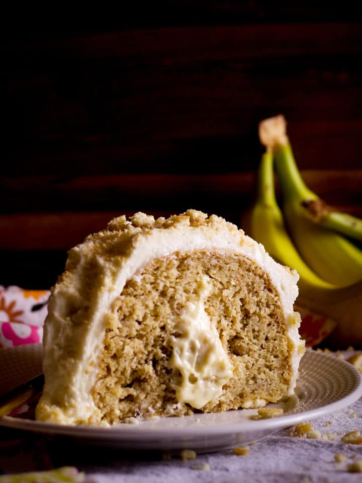 A slice of Banana Cream Cake on a plate with a fork.