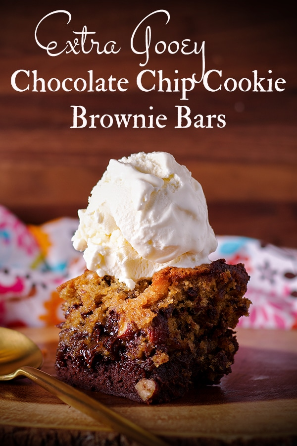 A chocolate chip cookie brownie bar on a wooden tray with a scoop of vanilla ice cream on top.