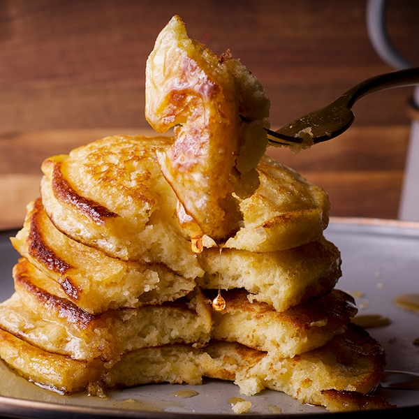 A plateful of homemade buttermilk pancakes covered in syrup with someone using a fork to take a bite.