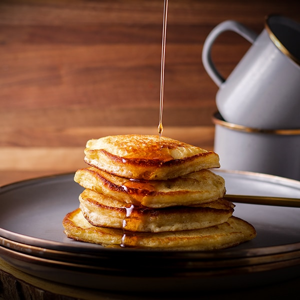 Pouring syrup over a stack of fluffy homemade buttermilk pancakes on a plate.