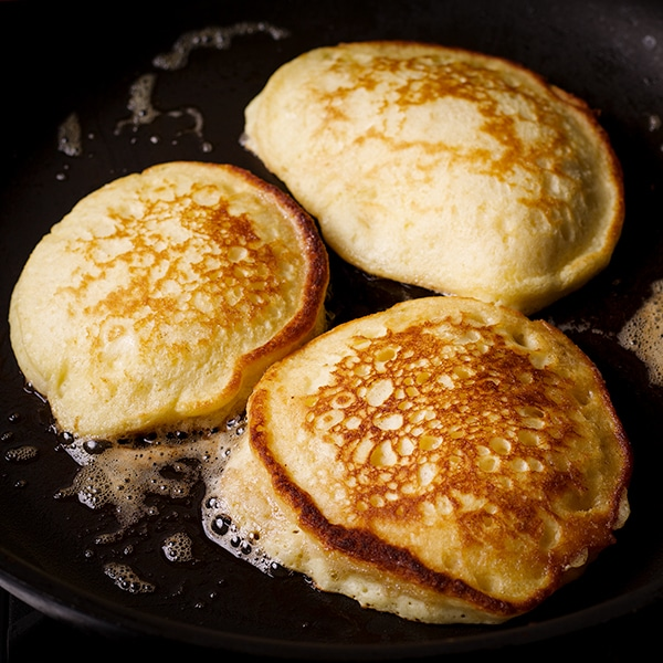 A skillet with three pancakes cooking in it.