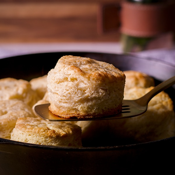 Lifting a buttermilk biscuit from a cast iron skillet.