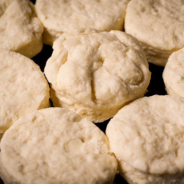 A cast iron pan with buttermilk biscuits in it that are ready to be baked.
