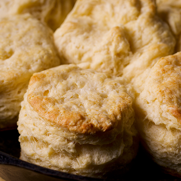 A cast iron pan with freshly baked buttermilk biscuits in it,