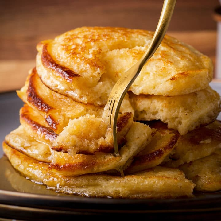 A plate of pancakes covered in syrup with a fork cutting into the stack of pancakes.