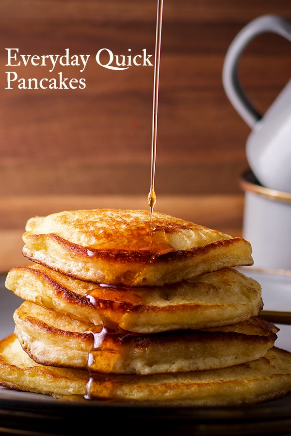 Pouring syrup over a stack of pancakes on a plate.