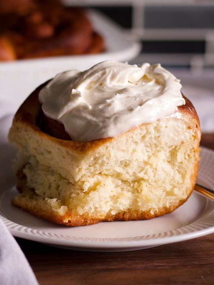 A homemade cinnamon roll covered in cream cheese buttercream sitting on a plate.