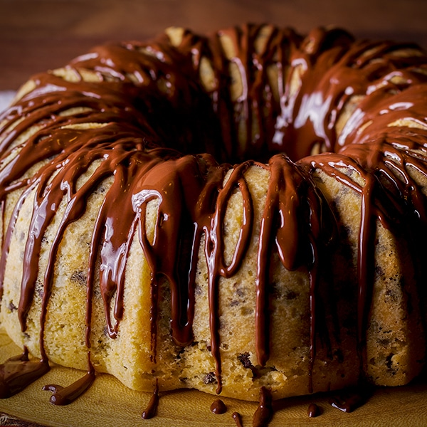 A chocolate chip Bundt Cake covered in chocolate peanut butter fudge icing on a wood serving platter.