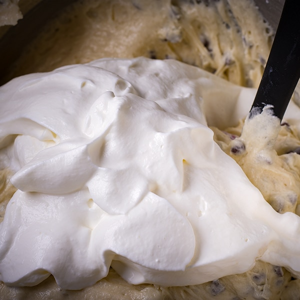Folding whipped cream into the batter for chocolate chip Bundt Cake.