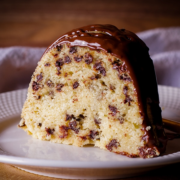 A slice of chocolate chip Bundt Cake on a plate, ready to eat.