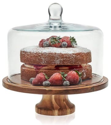 A cake stand with a wood base and glass top.