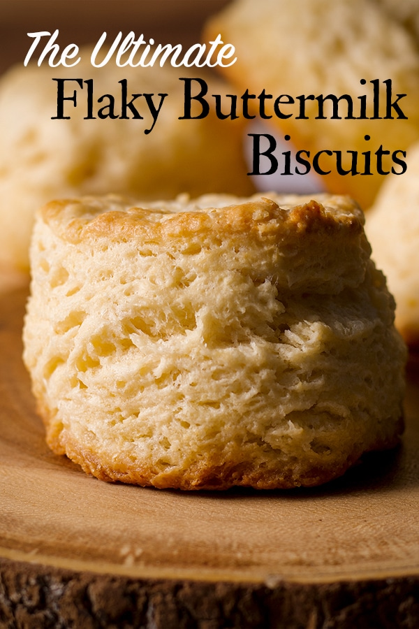A wood tray with several freshly baked buttermilk biscuits on it.
