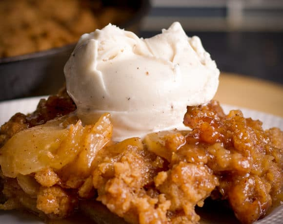 A serving of homemade apple cobbler on a plate, topped with a scoop of vanilla ice cream.