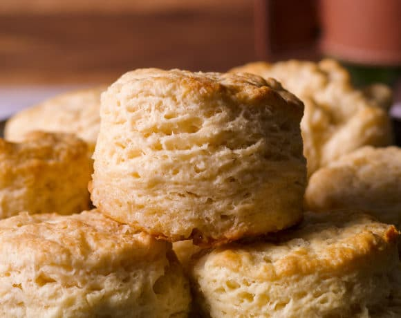 Several freshly baked buttermilk biscuits on a serving tray.