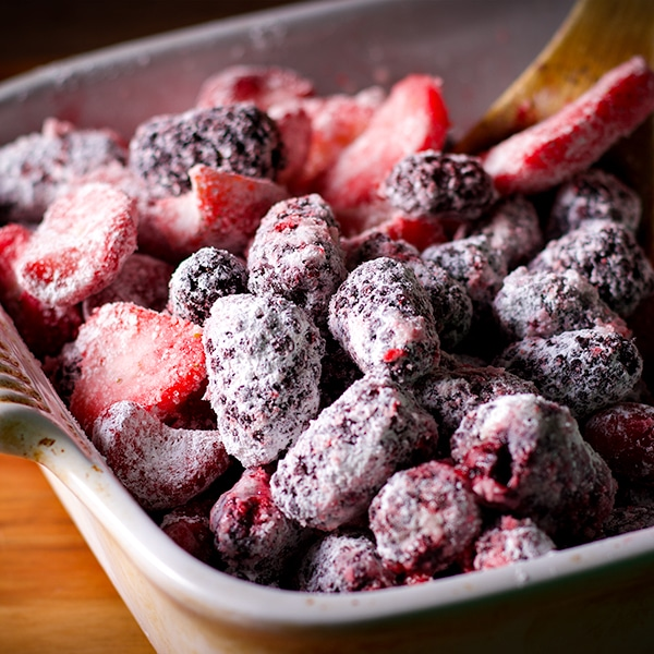 Frozen berries in a square baking dish to make berry cobbler.