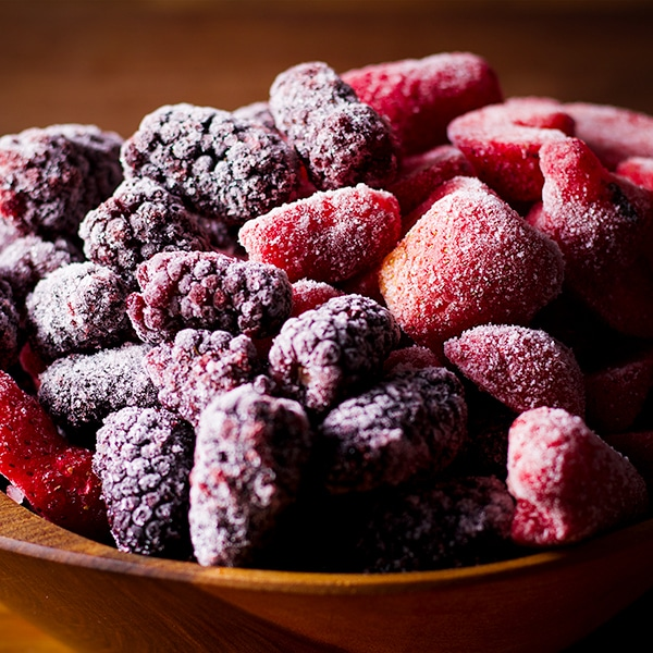 A wood bowl filled with frozen berries for berry cobbler.