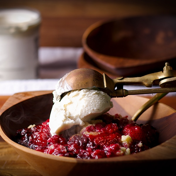 Topping a bowl of berry cobbler with a scoop of vanilla ice cream.