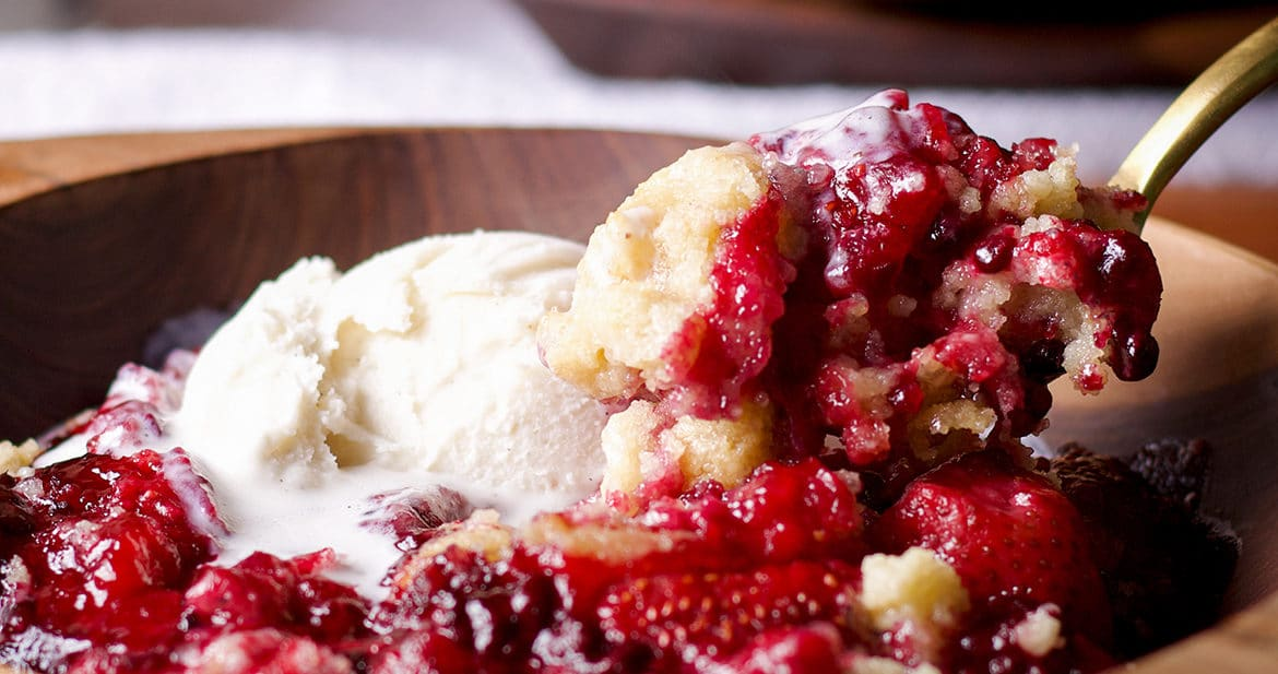 Using a spoon to scoop out a bite of warm homemade berry cobbler topped with ice cream.