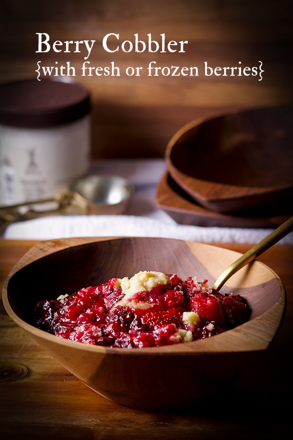 A wood bowl filled with berry cobbler and a gold spoon, ready to eat.