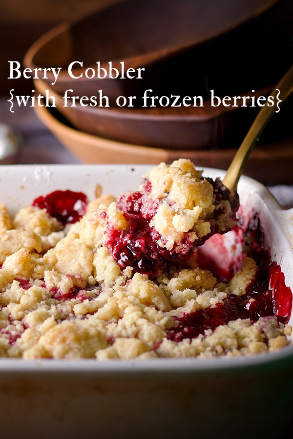 Using a gold spoon to scoop out some warm berry cobbler.