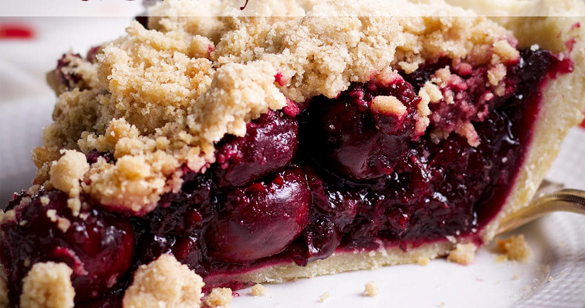 A white plate with a slice of sweet cherry crumb pie on it.