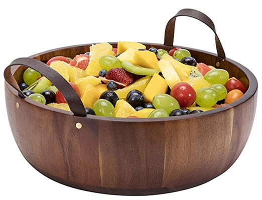 A large wood salad bowl with leather handles filled with fruit salad.