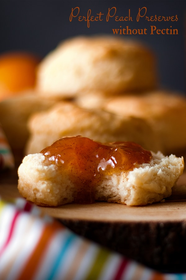 Homemade Peach Preserves spread on a biscuit with a bite taken out.