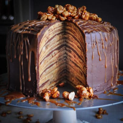 A chocolate banana split crepe cake covered in chocolate ganache, drizzled with peanut sauce, and topped with candy peanuts. One slice of the cake has been removed so you can see the layers inside.