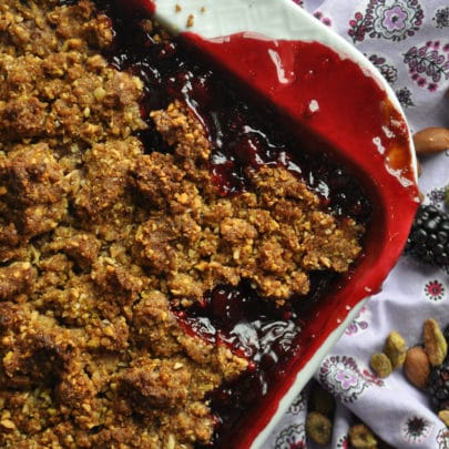 A freshly baked blackberry crisp with the fruit filling bubbling up over the edges of the pan.