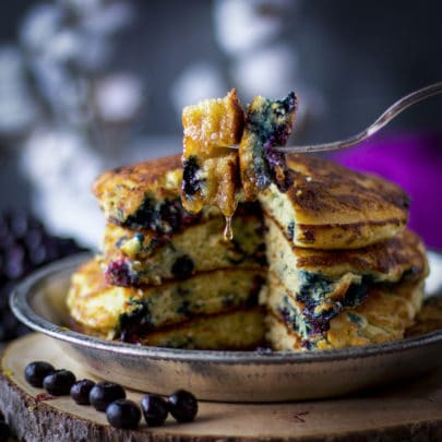 A fork with a bite of fluffy blueberry pancakes on it, syrup dripping from the pancakes, and a stack of blueberry pancakes in the background.