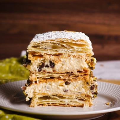 A Napoleon dessert made with pastry cream and puff pastry, cut in half so you can see the flaky layers of puff pastry and creamy layers of pastry cream.
