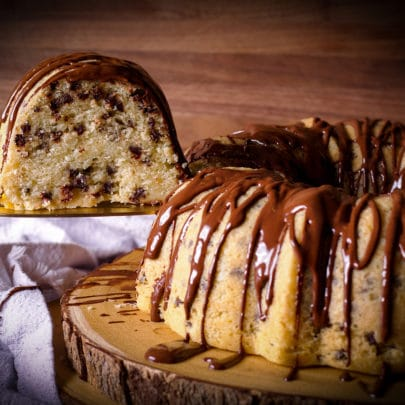 A chocolate chip Bundt Cake on a wood platter with someone using a spatula to lift a slice from the cake.