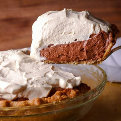 Someone using a spatula to lift a slice of chocolate cream pie from the whole pie so you can see the thick layers of chocolate cream and whipped cream.