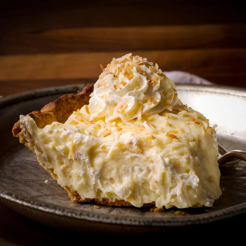A slice of coconut cream pie topped with a swirl of whipped cream and a sprinkle of toasted coconut on a tin plate.
