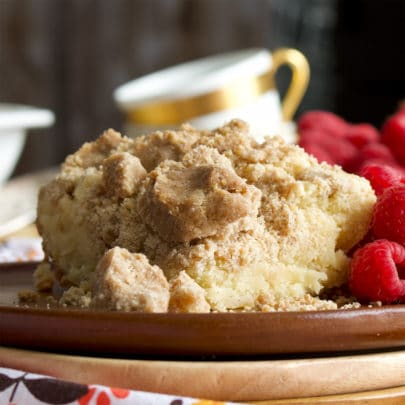 A piece of New York Style Crumb Cake on a wood plate with fresh raspberries.