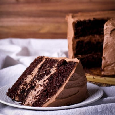 A thick slice of three layer Devil's Food cake frosted with chocolate buttercream on a white plate with the whole cake in the background.