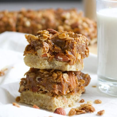 Two Dulce de Leche Granola Cookie Bars stacked one on top of the other. The top cookie has a bite taken out of it so you can see the gooey caramel center.
