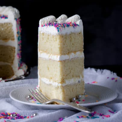 A slice of three layer gluten free vanilla cake frosted with buttercream and decorated with sprinkles on a plate with a fork.