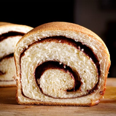 A loaf of homemade cinnamon bread that's been cut in half so you can see the buttery cinnamon swirl in the middle.