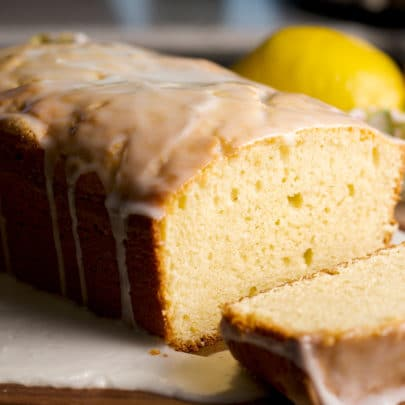 A lemon loaf cake covered in lemon glaze with the first slice cut from it so you can see the soft, tender interior of the cake.