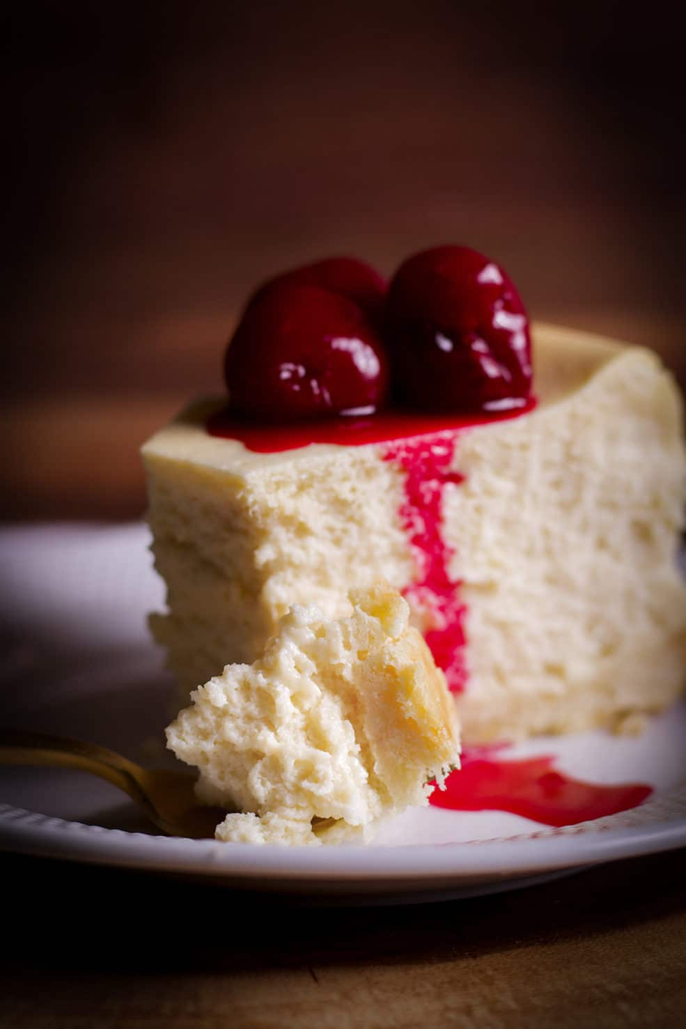 A close up shot of a bite of creamy New York Cheesecake on a fork with the rest of the slice of cheesecake behind it.