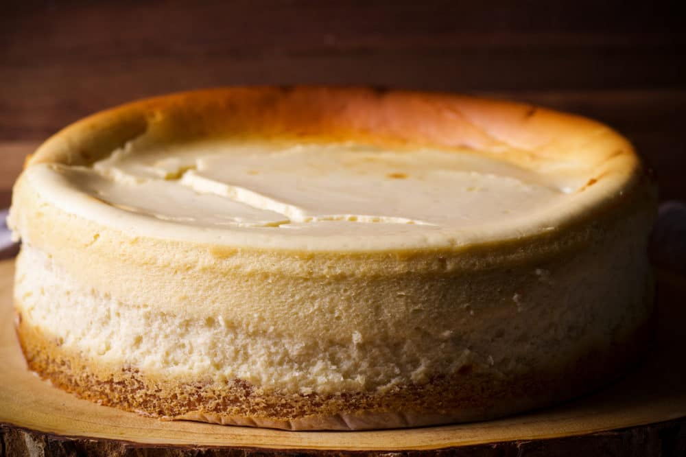 A New York Cheesecake on a wood platter.