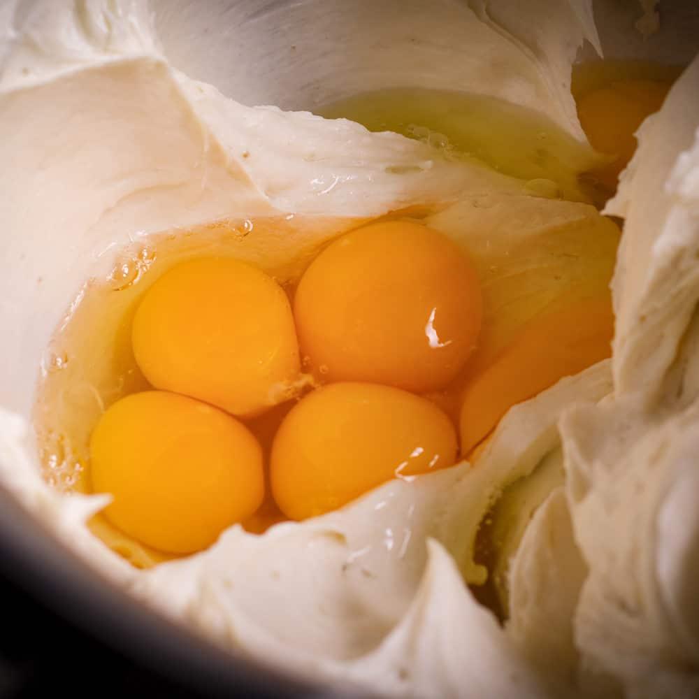 Adding eggs to New York Cheesecake Batter.