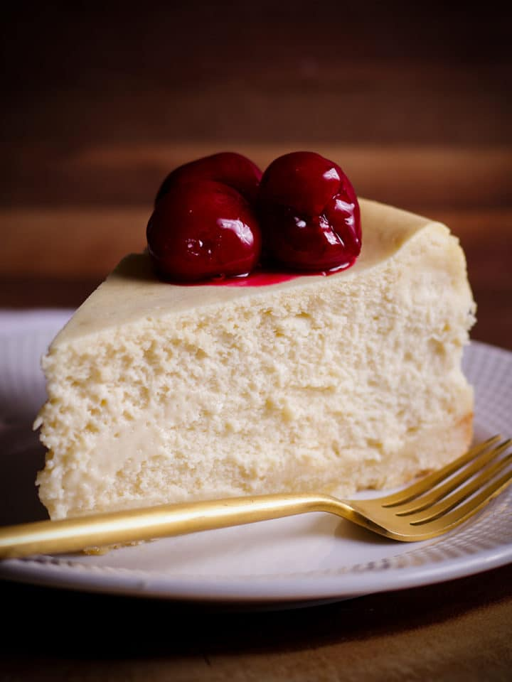 A thick slice of New York Cheesecake with cherry sauce on top on a white plate with a gold fork.