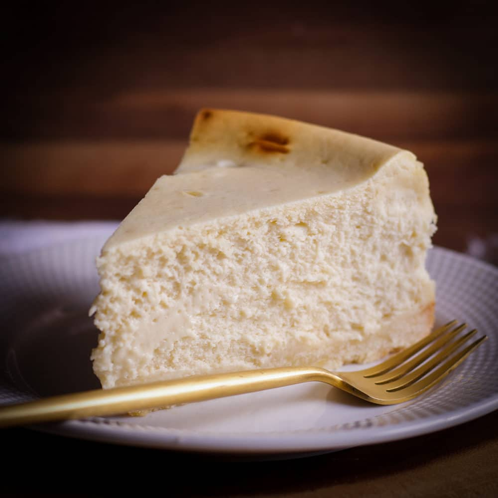 A thick slice of New York Cheesecake on a white plate with a gold fork.